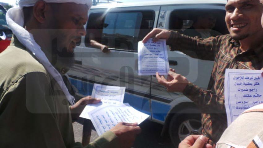 بالصور.. أنصار مرسي يوزعون منشورات بشارع رمسيس