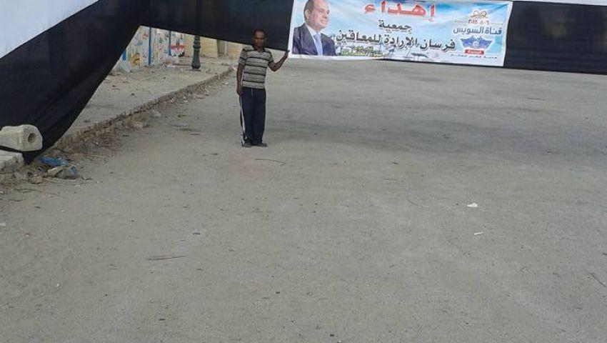 بالصور|معاقو سيناء يحتفلون بالقناة برفع علم طوله 40 متراً