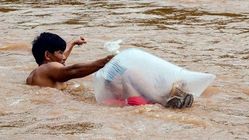 بالصور| في أكياس بلاستيك.. أطفال يعبرون النهر طلبا للعلم